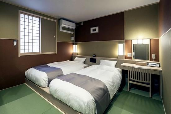 <和空 下寺町>客室は畳の上にベッドが置かれ落ち着いたデザイン